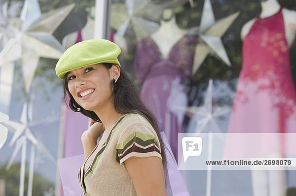 Side profile of a young woman carrying a shopping bag and smiling