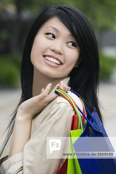 Close-up of a young woman carrying shopping bags and smiling