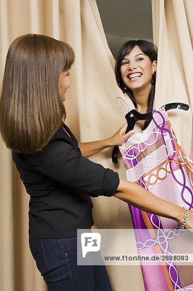Side profile of a sales clerk giving a dress to a young woman in a fitting room