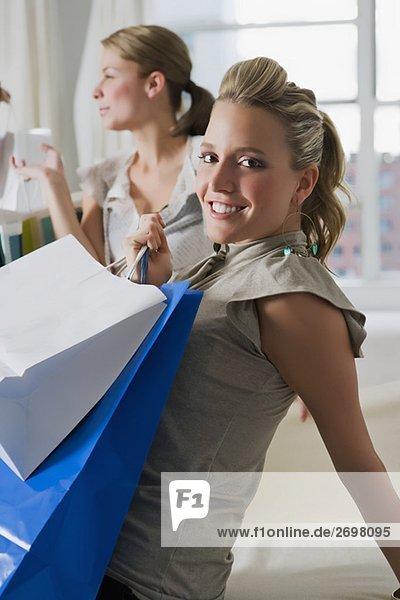 Portrait einer jungen Frau Einkaufstaschen tragen und ihre Freundin sitzen im Hintergrund