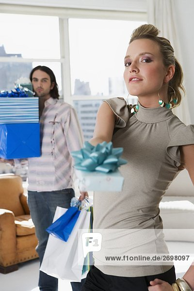 Portrait of a young couple holding gifts and shopping bags
