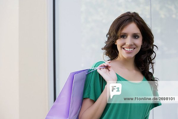Portrait of a young woman carrying a shopping bag and smiling