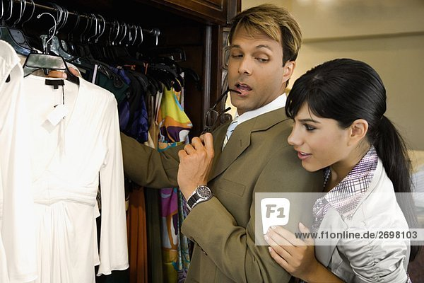 Side profile of a mid adult man with a young woman choosing a dress in a clothing store