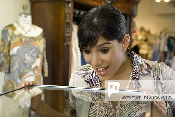Young woman looking in a display cabinet with a surprise