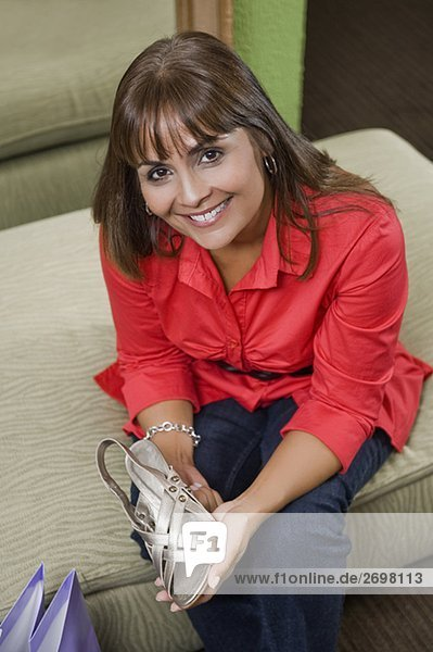 Portrait of a sales clerk holding a sandal and smiling