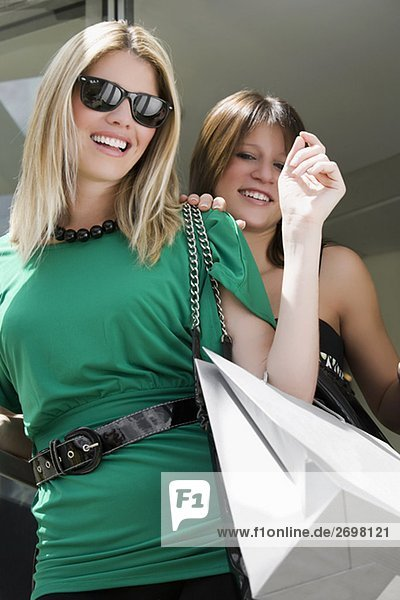 Low angle view of two young women carrying shopping bags and smiling