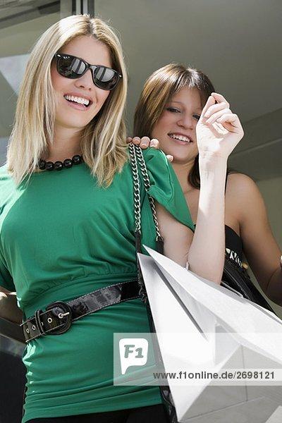 Untersicht von zwei jungen Frauen tragen Tragetaschen und lächelnd
