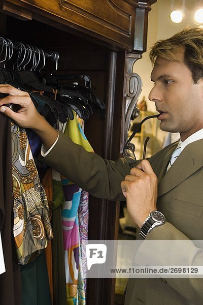 Side profile of a mid adult man choosing a dress in a clothing store