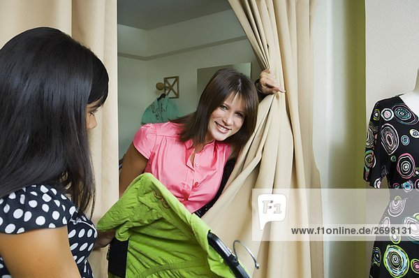 Side profile of a sales clerk giving a dress to a young woman