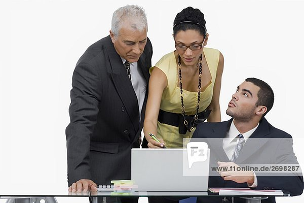 Two businessmen and a businesswoman discussing on a laptop in an office