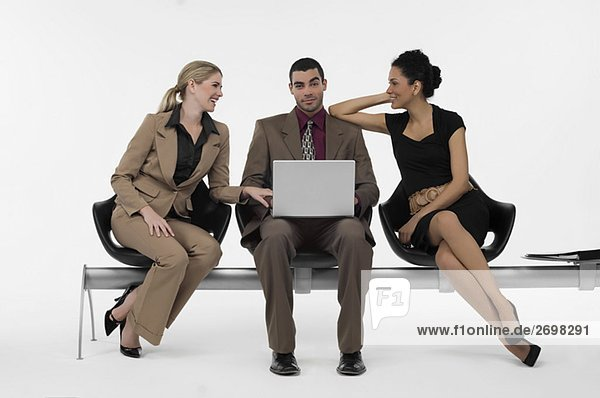 Businessman using a laptop and two businesswomen sitting beside him