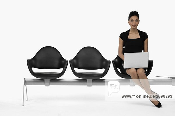 Portrait of a businesswoman sitting on a bench and using a laptop