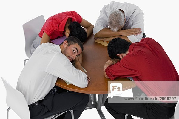 High angle view of three businessmen and a businesswoman resting their heads on a table