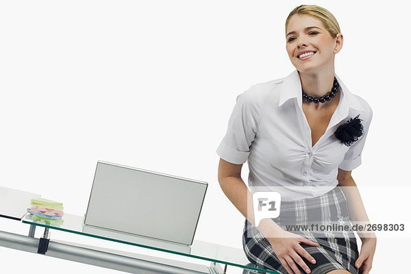 Businesswoman sitting on a table and smiling