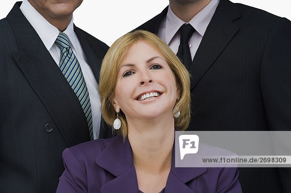 Portrait of a businesswoman smiling with two businessmen behind her
