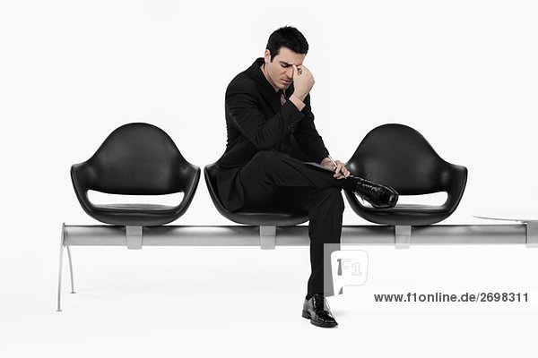 Businessman sitting on a bench and thinking