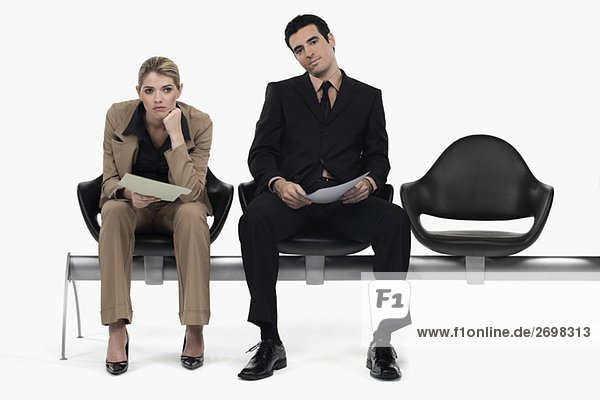 Businessman and a businesswoman sitting on a bench