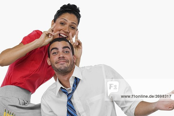 Portrait of a businesswoman gesturing behind a businessman and smiling