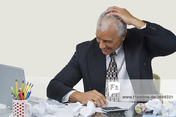 Businessman sitting at a desk in an office and smiling