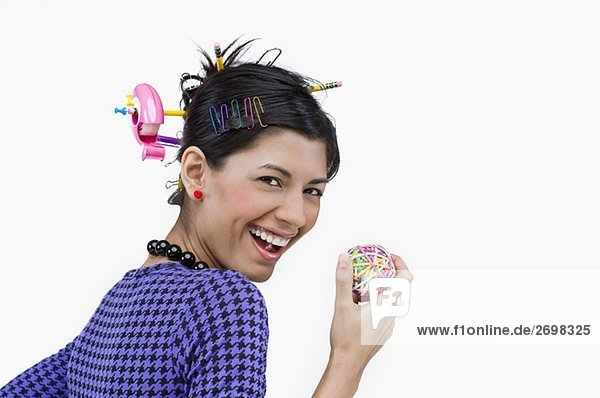 Portrait of a young woman holding rubber bands and smiling