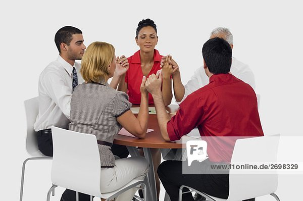 Three businessmen and two businesswomen praying with holding their hands in a meeting