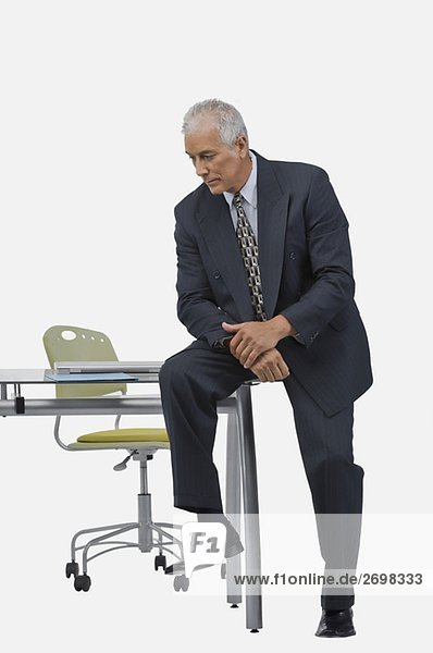 Businessman sitting at a desk in an office and thinking