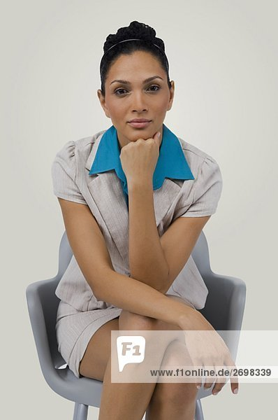 Portrait of a businesswoman sitting on a chair with her hand on her chin