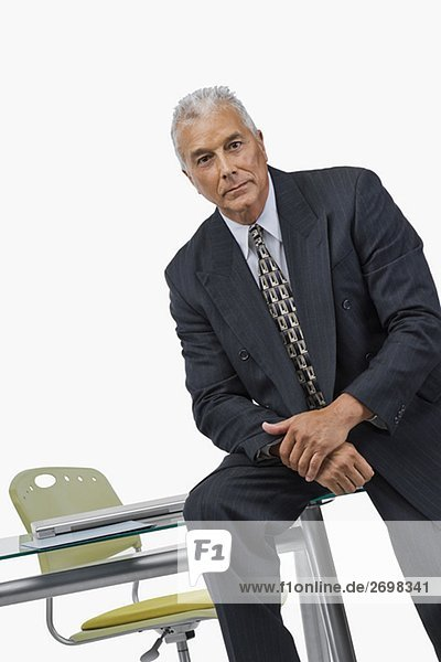 Portrait of a businessman sitting on a desk in an office