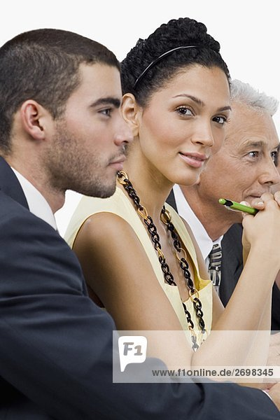 Two businessmen and a businesswoman at a meeting in a conference room