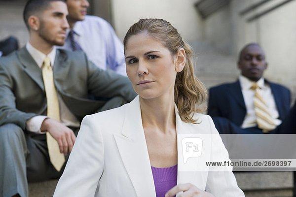 Nahaufnahme der geschäftsfrau mit drei Geschäftsmänner sitzen hinter ihr