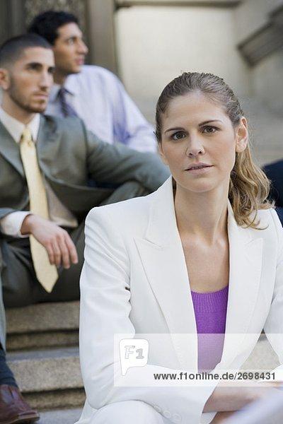 Nahaufnahme der Geschäftsfrau sitzt auf Schritte mit zwei Geschäftsleute hinter ihr