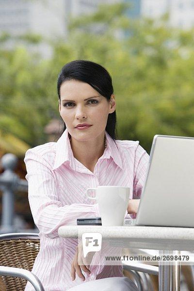 Porträt von Geschäftsfrau sitzt auf einem Stuhl und benutze ein laptop