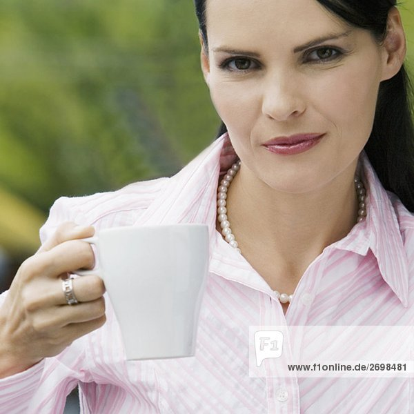 Portrait of a mid adult woman holding a cup of coffee and smiling