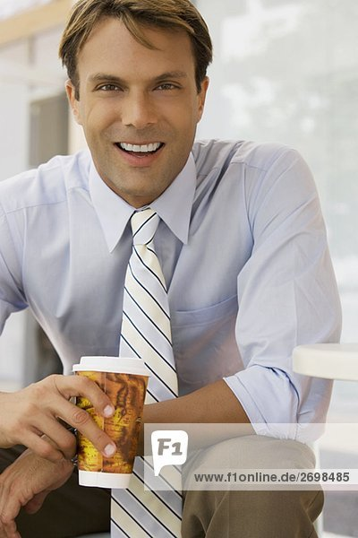Portrait of a businessman holding a coffee cup and smiling