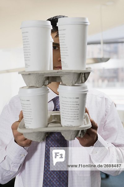 Portrait of a businessman holding disposable cups