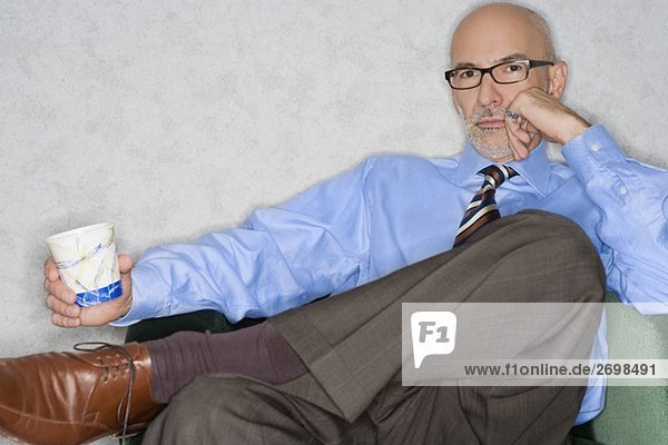 Portrait of a businessman sitting in an armchair and holding a glass