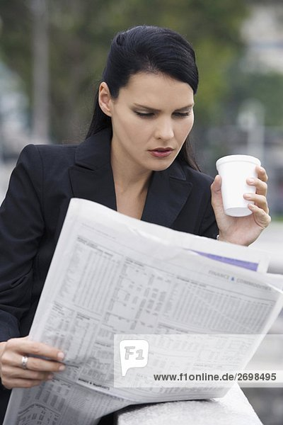 Close-up of a businesswoman reading a newspaper