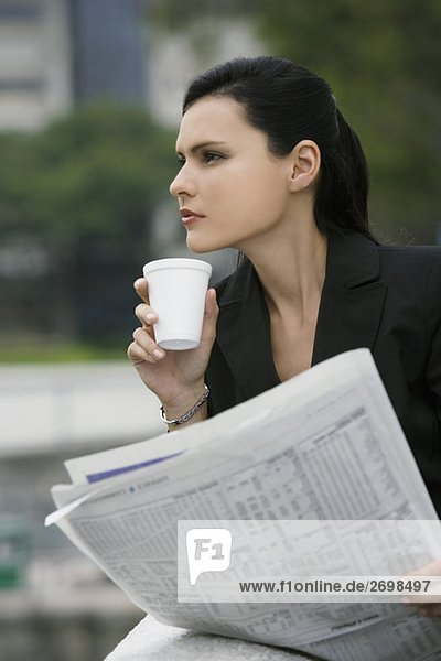 Close-up of a businesswoman holding a newspaper and thinking