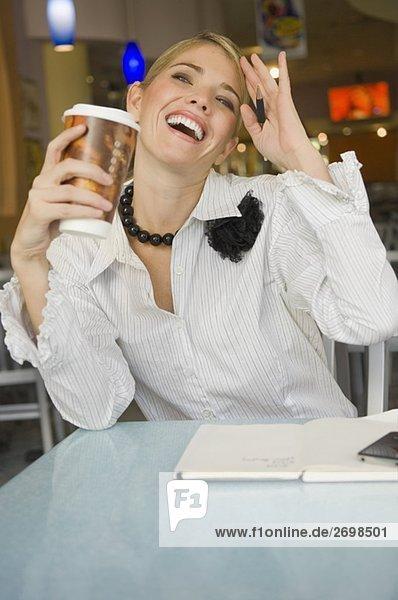 Geschäftsfrau hält eine Pappbecher und lächelnd in einem restaurant