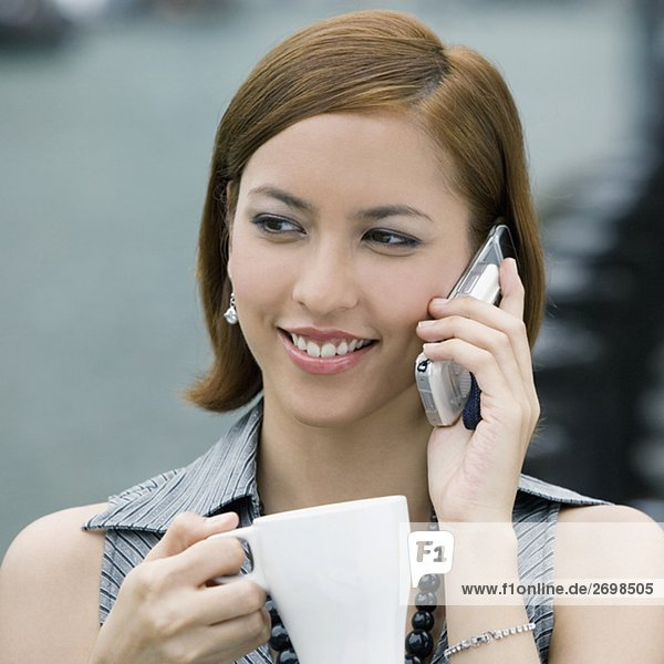 Close-up of a young woman holding a coffee cup and talking on a mobile phone