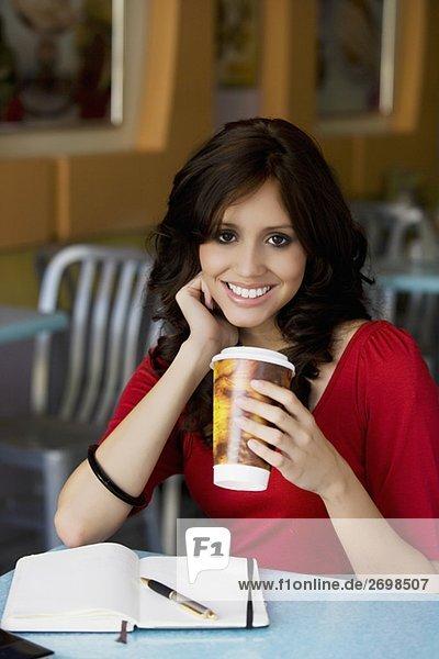 Portrait einer jungen Frau hält eine Tasse kaltes Getränk und lächelnd