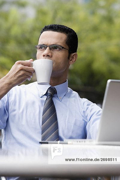 Close-up of a businessman sitting in front of a laptop and drinking coffee