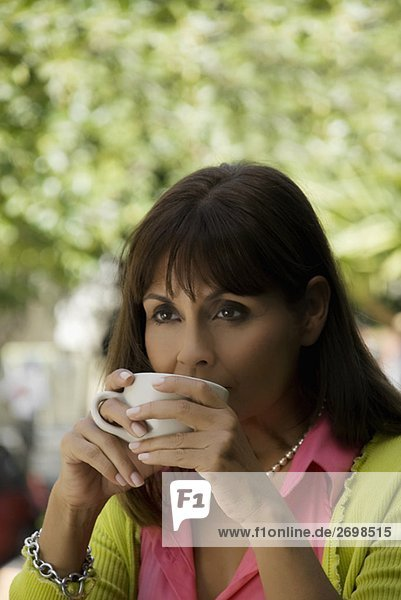 Close-up of a mature woman drinking a cup of coffee