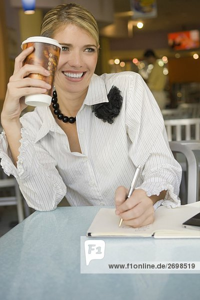 Businesswoman writing in a diary and smiling in a restaurant