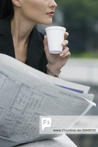 Close-up of a businesswoman holding a disposable cup and a newspaper