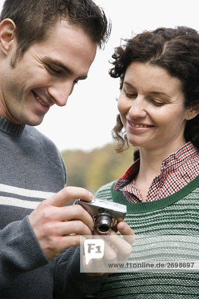 Close-up of a couple looking at a digital camera