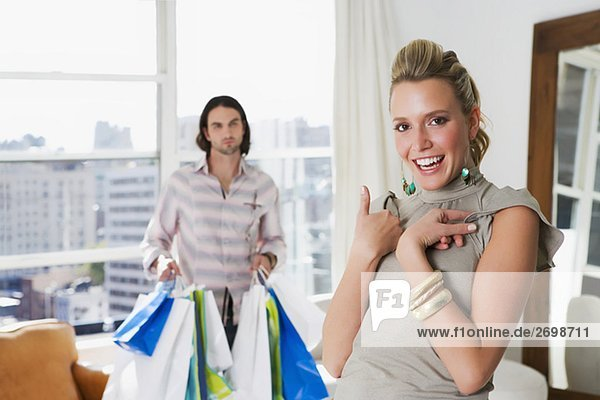 Young woman laughing with a young man holding shopping bags behind her