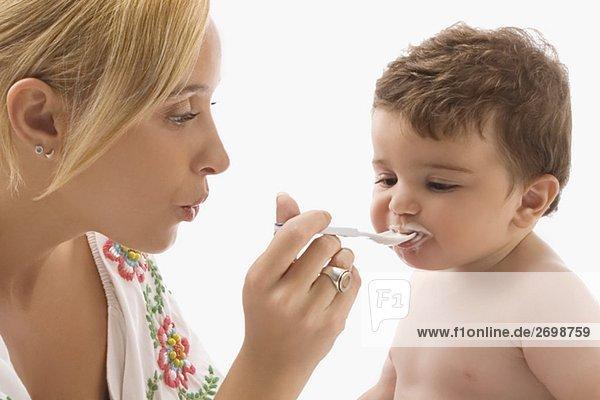 Nahaufnahme einer Mitte erwachsen Frau ihr Sohn mit einem Löffel füttern