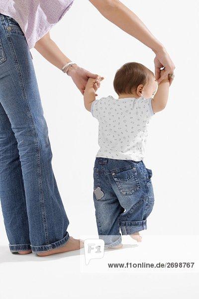 Rückansicht eines jungen Baby hält hände seiner Mutter