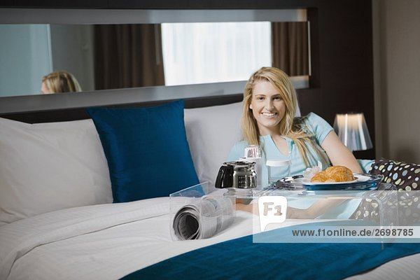 Portrait einer jungen Frau dem Frühstück auf dem Bett